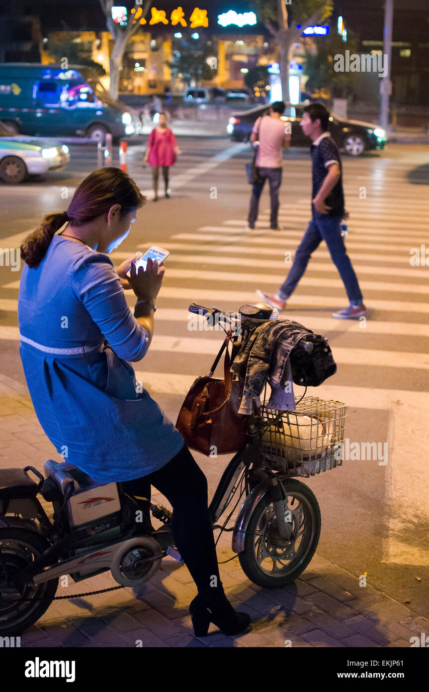 Young woman checks smart phone while on electric scooter, Anyang, Henan Province, China. - Stock Image