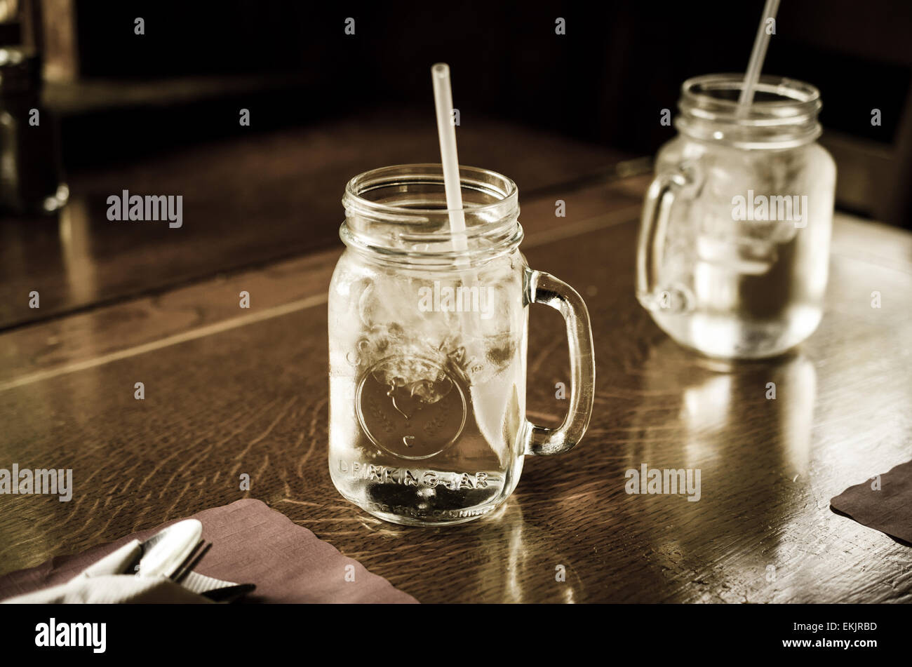 Mason jars sitting on a country table. - Stock Image