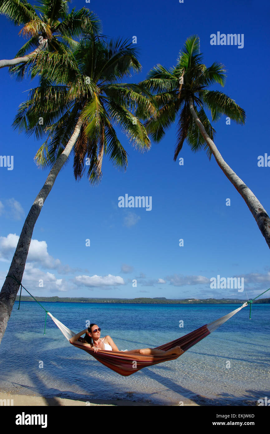 Young woman in bikini laying in a hammock between palm trees, Ofu island, Vavau group, Tonga - Stock Image
