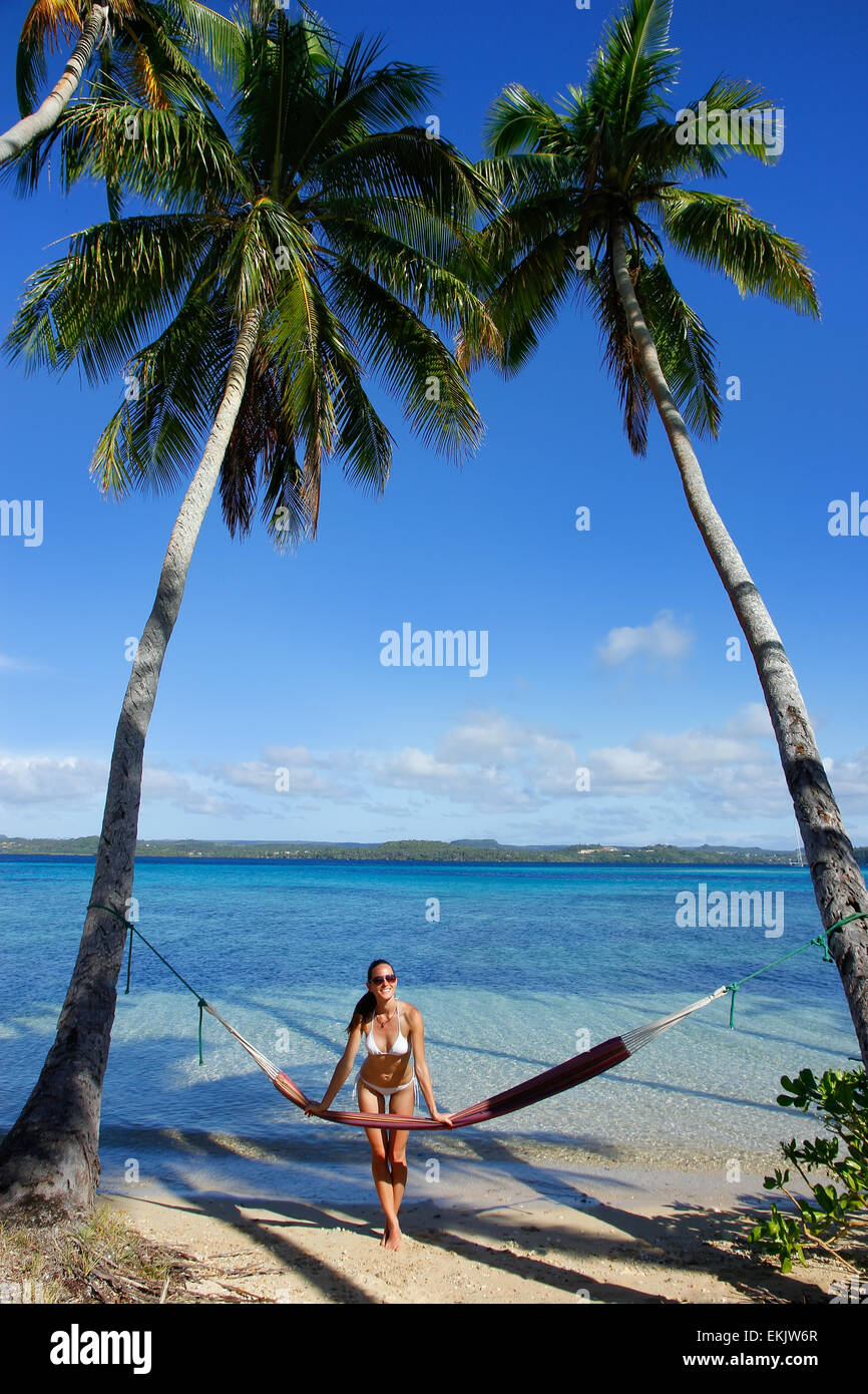 Young woman in bikini standing by the hammock between palm trees, Ofu island, Vavau group, Tonga - Stock Image