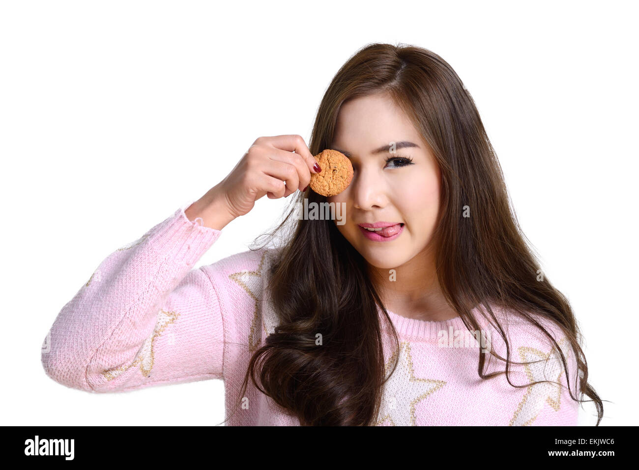 Cute girl in pink sweater on white background make funny action by bring cookie closed her eye and show her tongue. - Stock Image