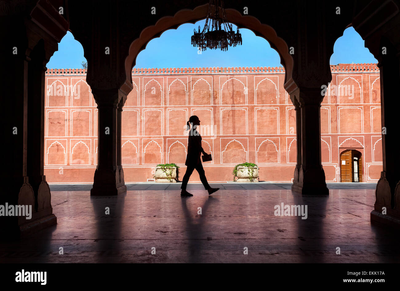 Woman silhouette with guidebook walking in the City Palace museum, Jaipur, Rajasthan, India - Stock Image
