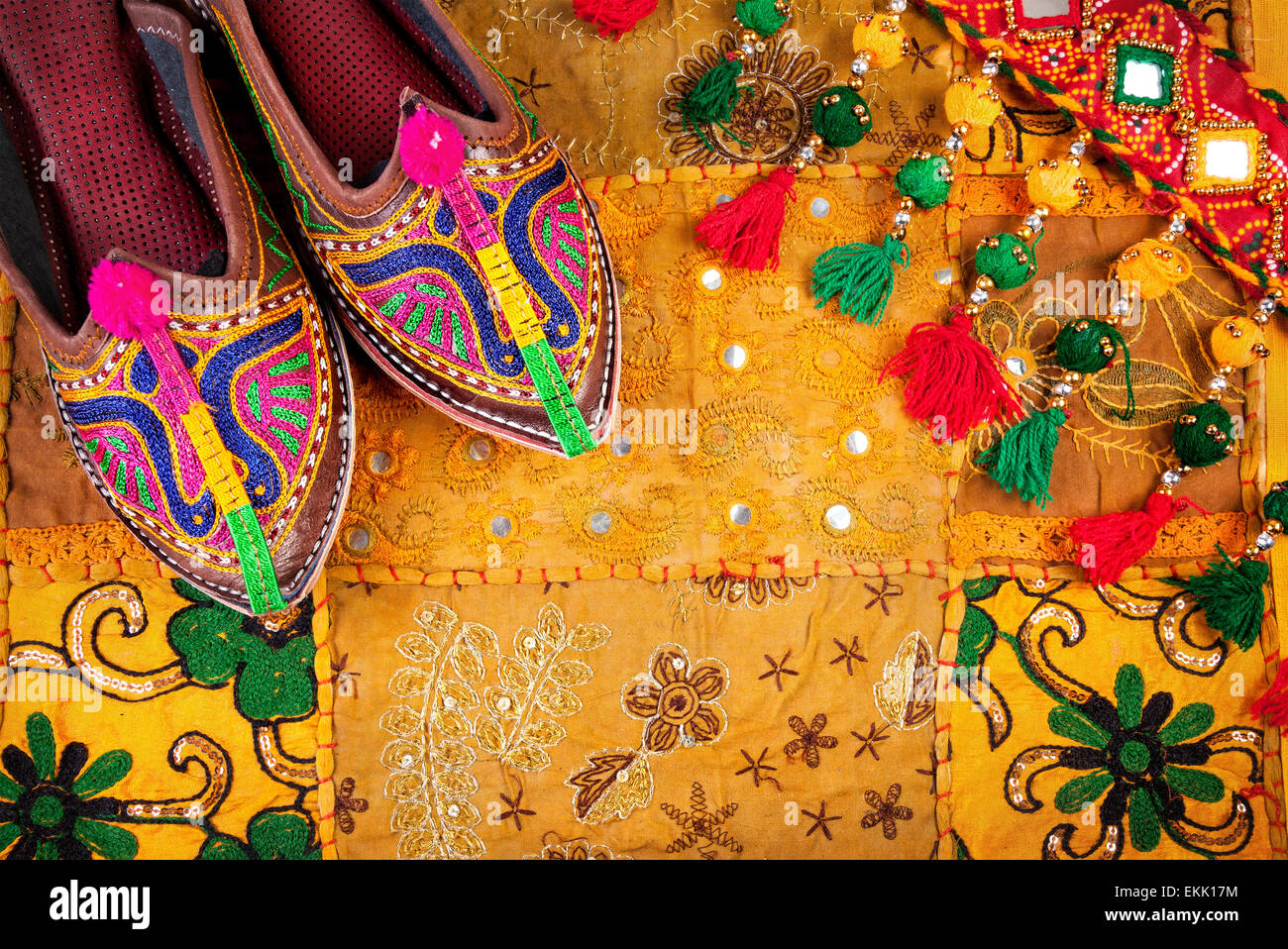 Colorful ethnic shoes and gipsy belt on yellow Rajasthan cushion cover on flea market in India - Stock Image