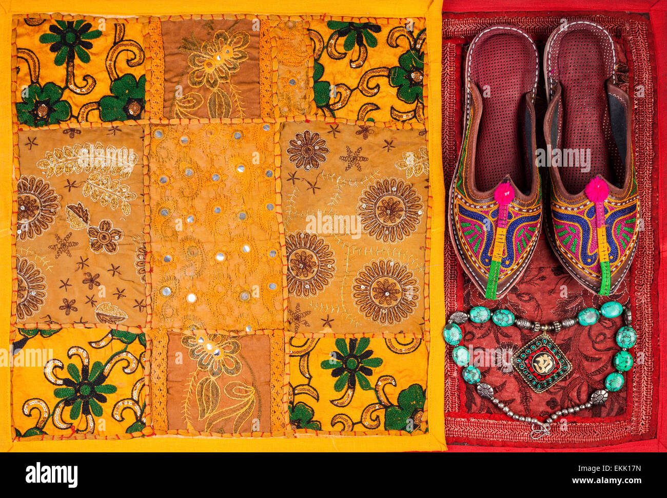 Colorful ethnic shoes, necklace and yellow Rajasthan cushion cover on flea market in India - Stock Image