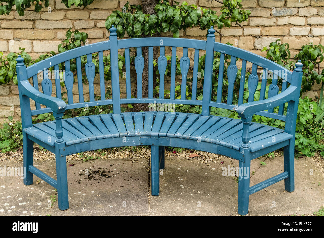 Blue Wooden Garden Bench Seat In Front Of Old Stone Wall