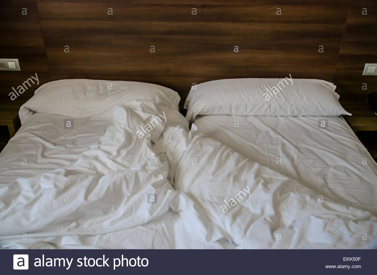 Empty messy bed after a night of sleeping - Stock Image