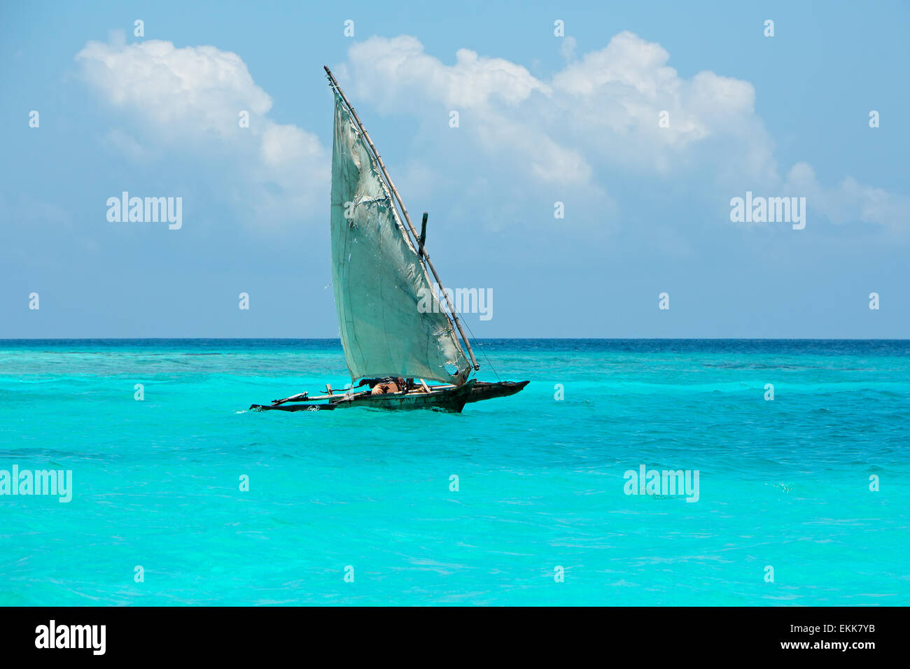 Wooden sailboat  (dhow) on the clear turquoise water of Zanzibar island - Stock Image