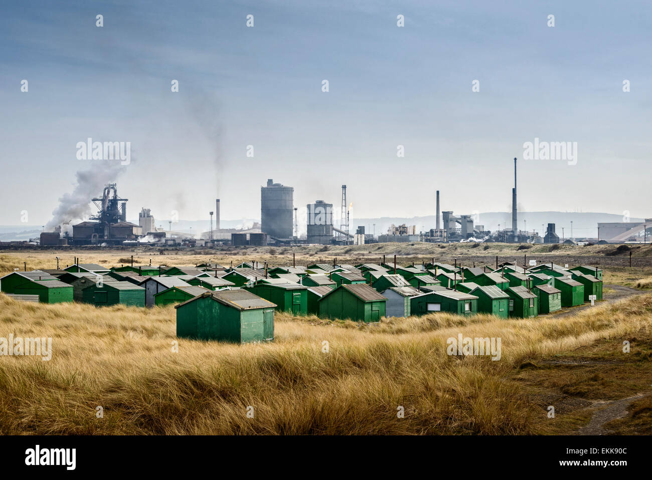 Fishermen's huts at South Gare in Redcar with the Sahaviriya Steel Industries UK (SSI) Steel Plant in the background. - Stock Image