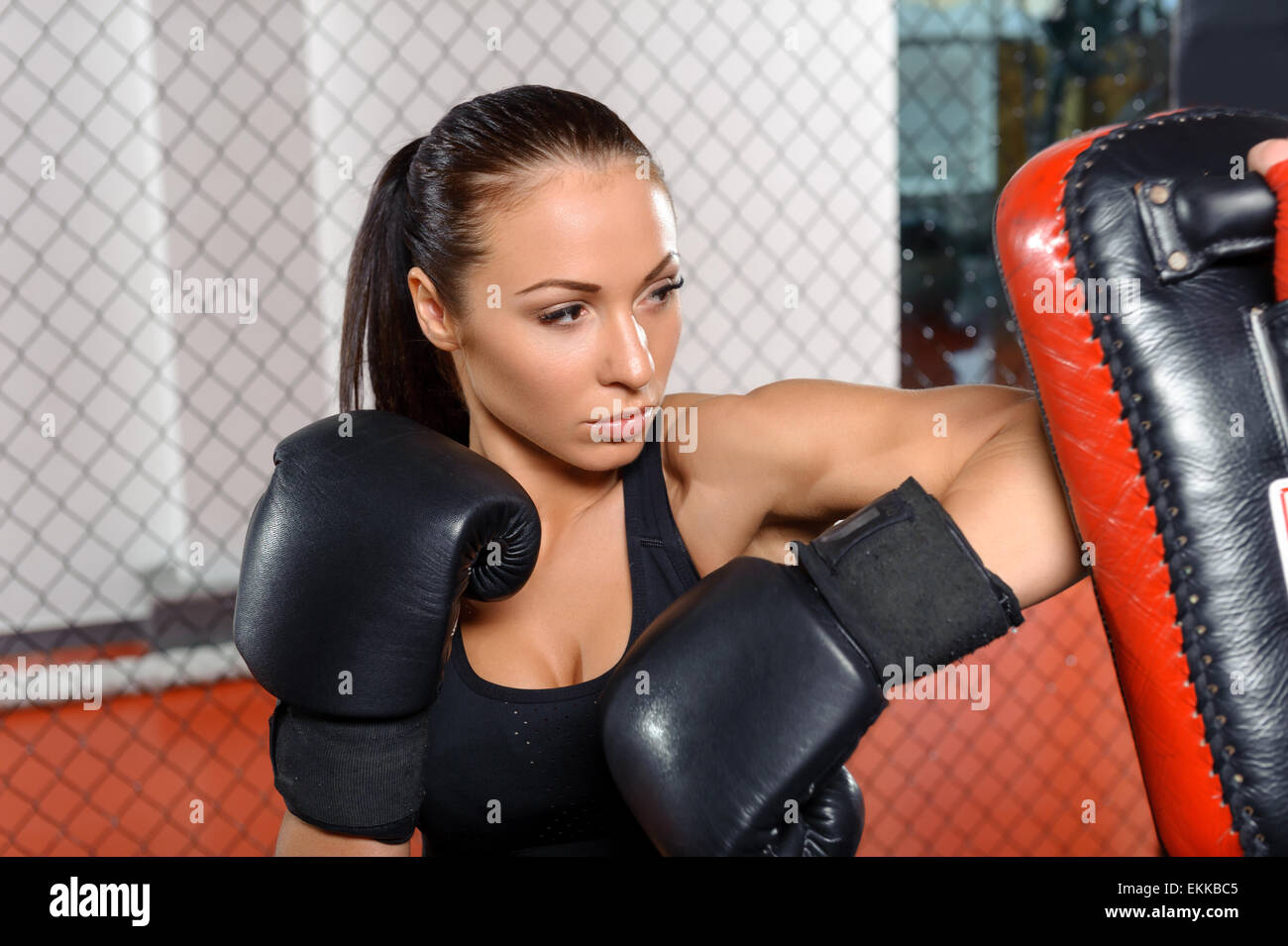 Female fighter trains in a fighting cage - Stock Image