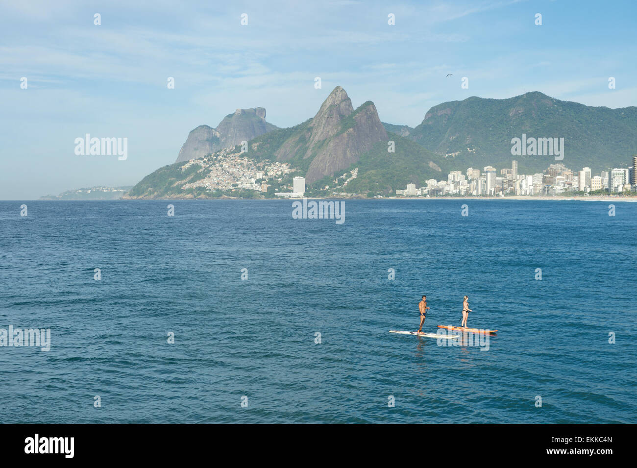 RIO DE JANEIRO, BRAZIL - MARCH 22, 2015: A pair of stand up paddle enthusiasts make their way along the water at - Stock Image