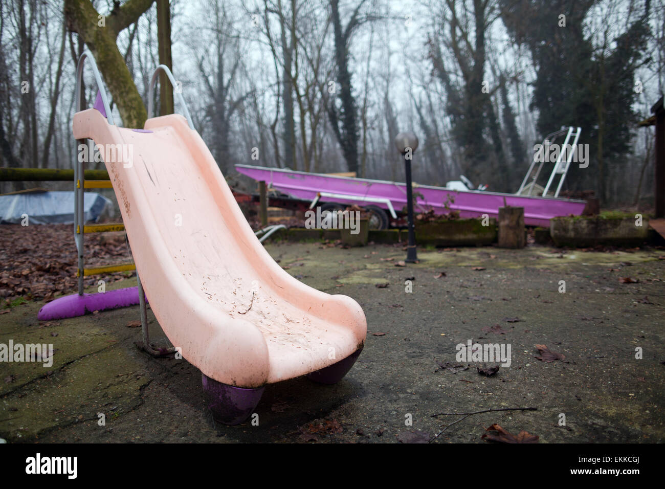 Pink slide and fuchsia boat in a misty woodland - Stock Image