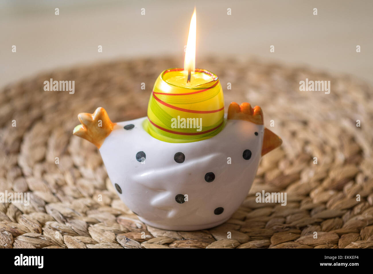 Easter candlestick in the shape of chicken with burning candle - Stock Image