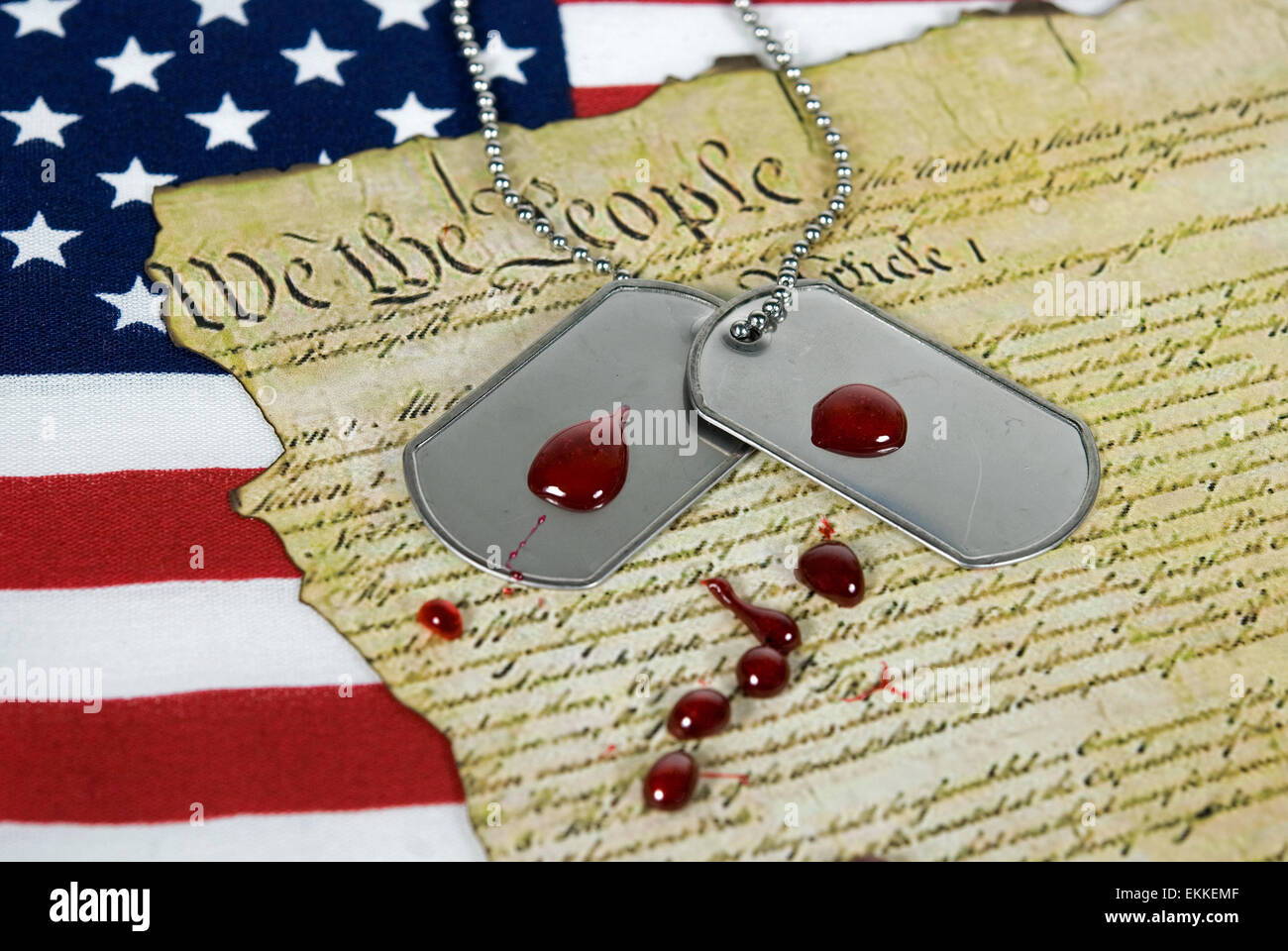 Blood drops on military dog tags on the United States Constitution document with flag. - Stock Image