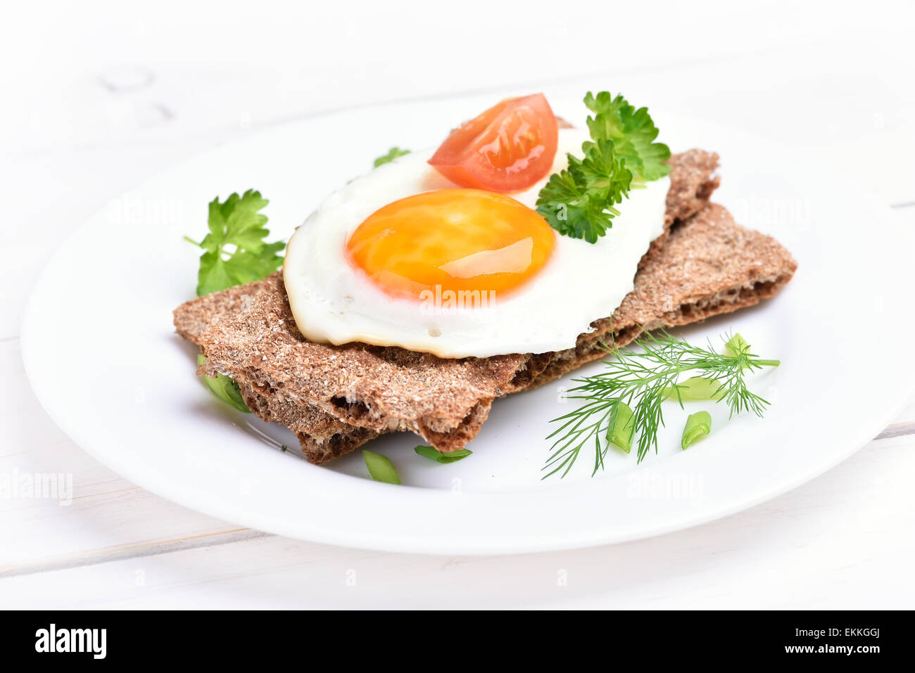 Fried egg on crispbread, close up view - Stock Image