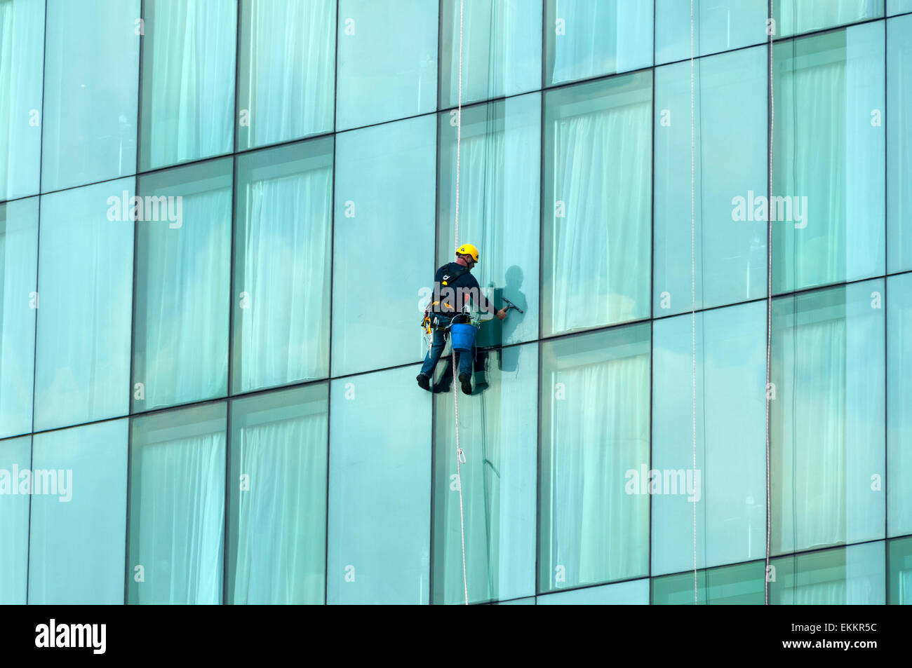 Window cleaner suspended on a rope on the Beetham Tower, Deansgate, Manchester, England, UK - Stock Image