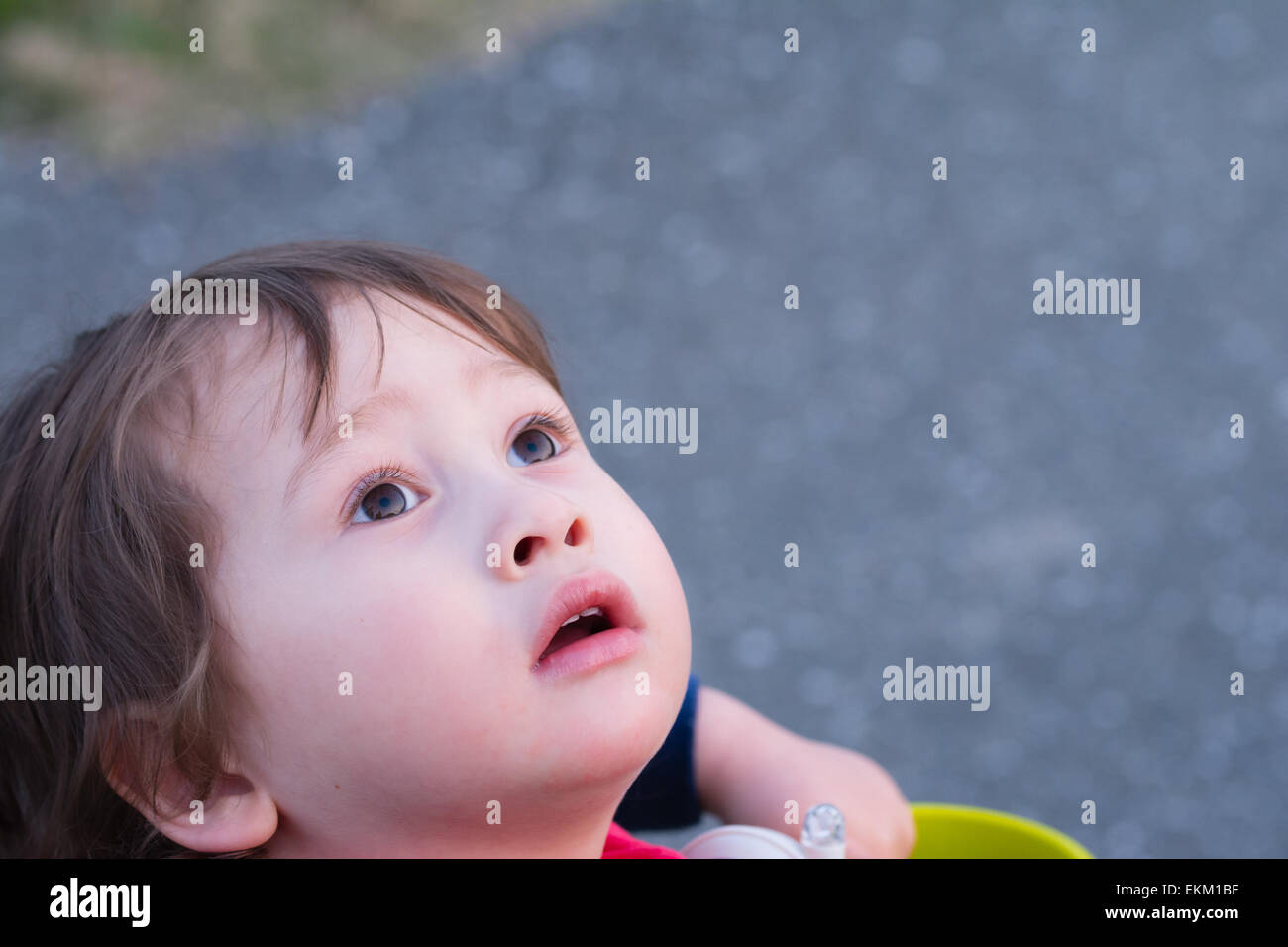 A 2 year old boy staring off into the sky. - Stock Image