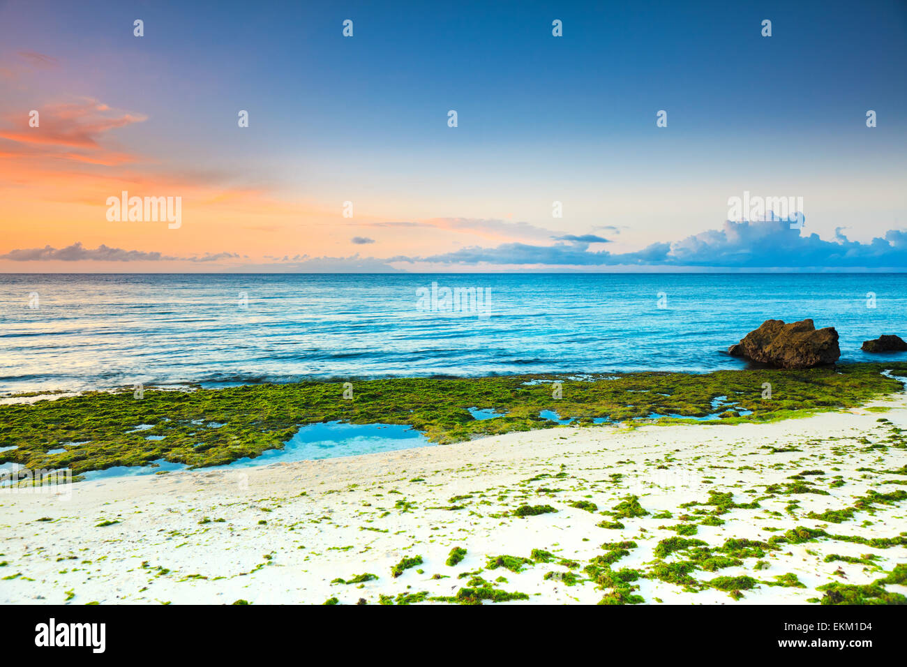 Sunrise over the sea. Stone on the foreground - Stock Image