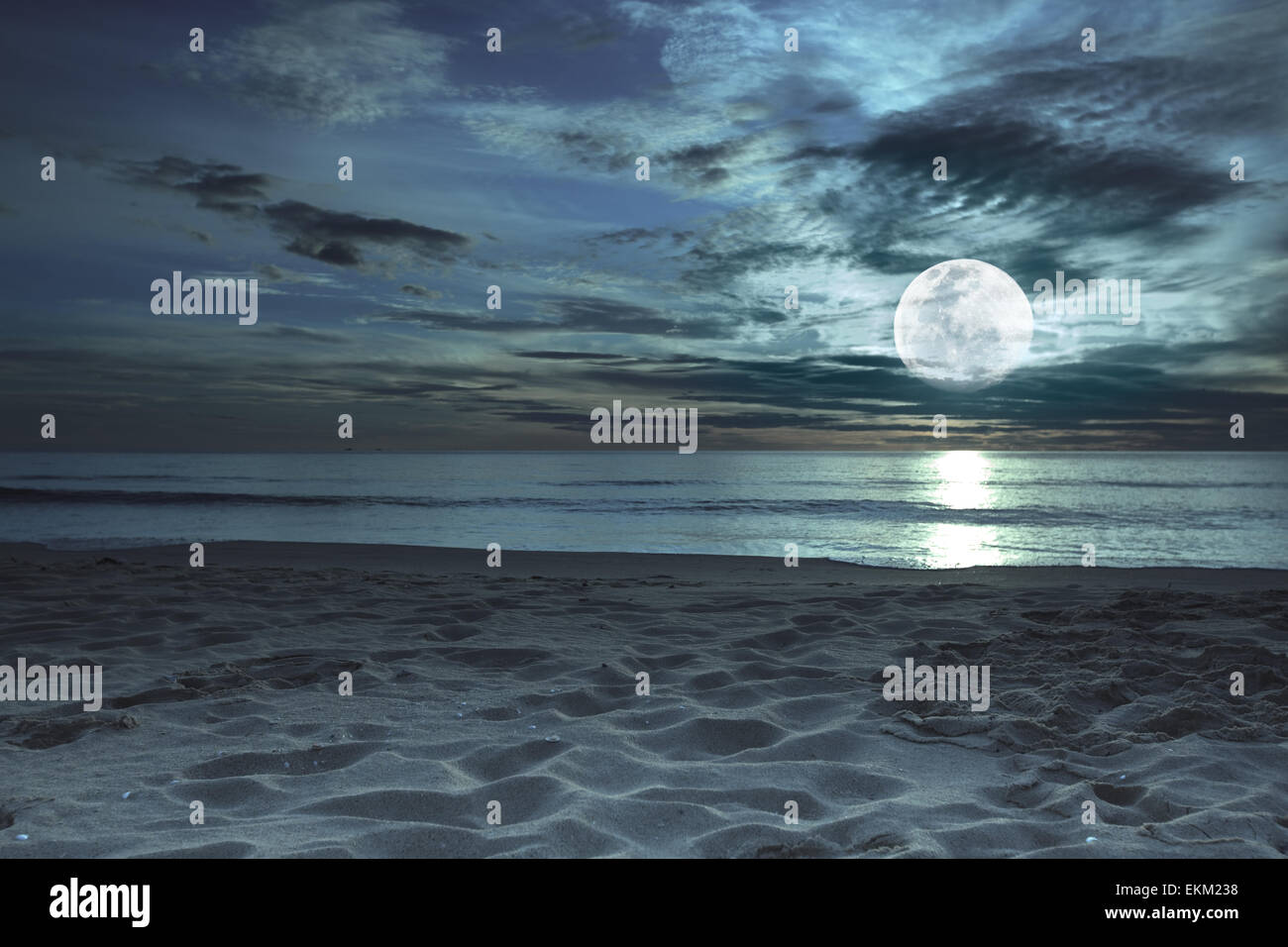 Beautiful beach at twilight time with moon in the sky - Stock Image