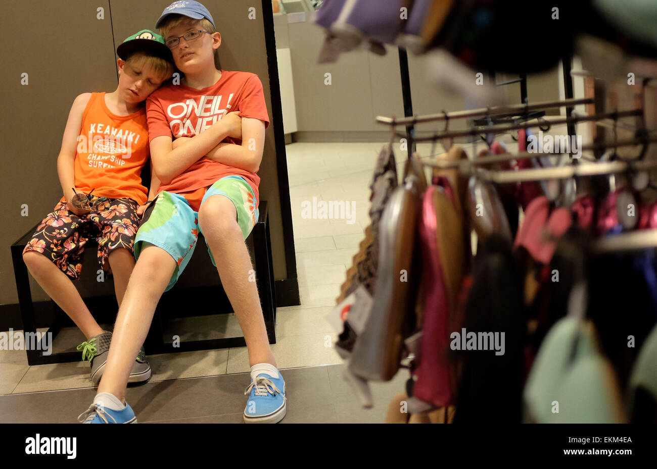 9028713c7f8e4b bored children wait for their mother to finish shopping in a shoe shop -  Stock Image