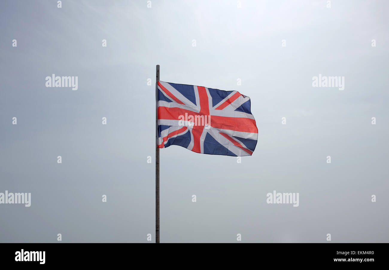 Union Flag flying against a white background sky - Stock Image
