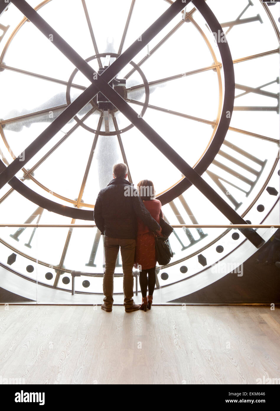 A romantic couple peek through the Orsay Clock in the Musée d'Orsay in Paris - Stock Image
