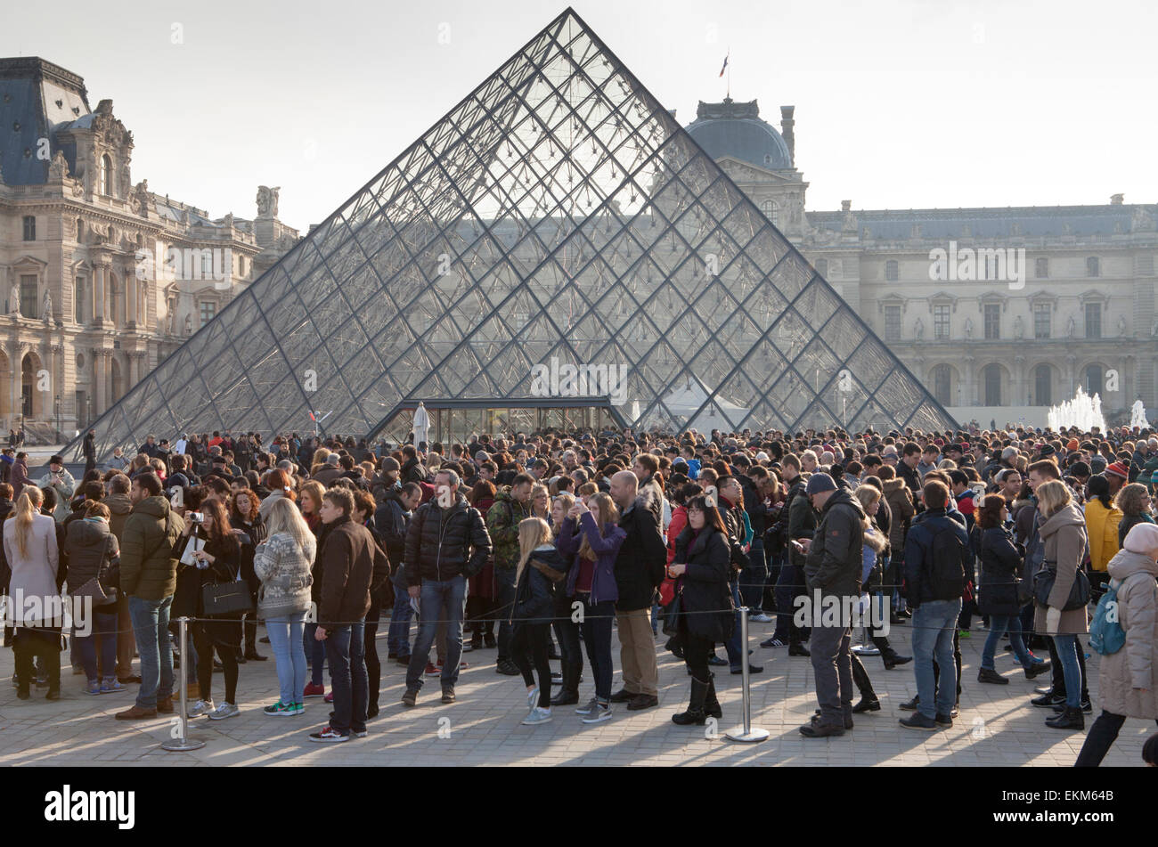 The queue of visitors at the Louvre Pyramid and Palace in Paris Stock Photo