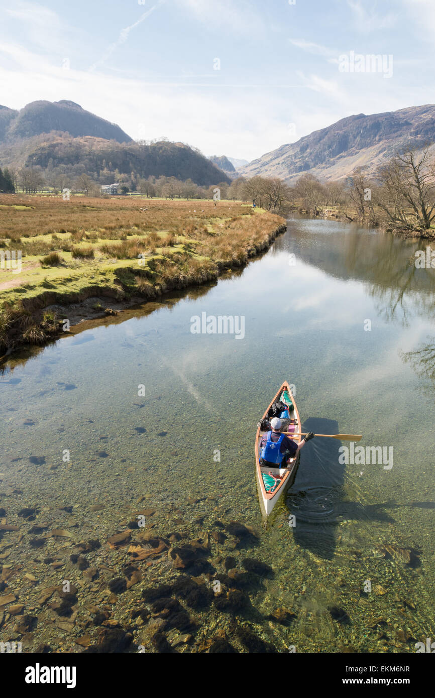 Man and dog viewed from the Chinese Bridge paddling canoe along river Derwent close to Derwentwater in the English - Stock Image