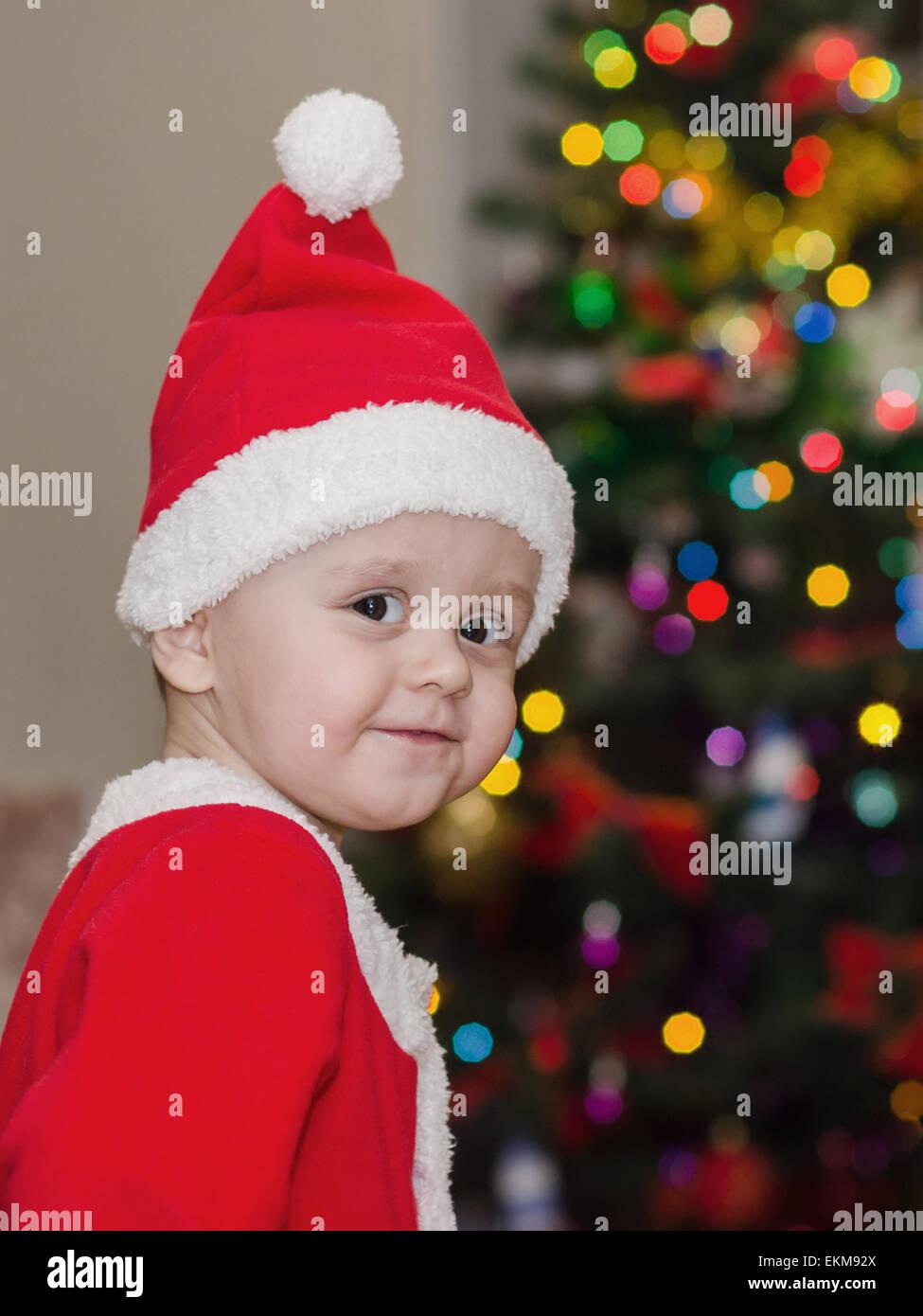 Little kid dressed as Santa Claus standing near Christmas Tree Stock ...