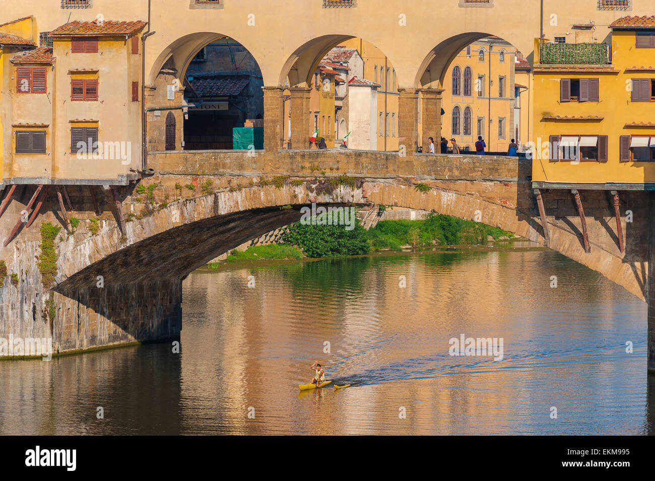 Florence summer River Arno, view of a man in a canoe rowing beneath the Ponte Vecchio in Florence, Italy. Stock Photo