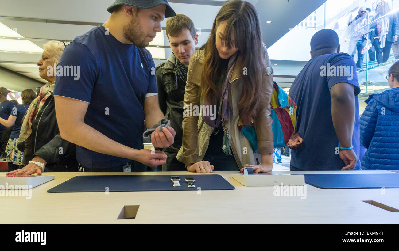 New York, USA. 12th April, 2014. An employee in an Apple Store in New York assists a shopper about the Apple Watches - Stock Image