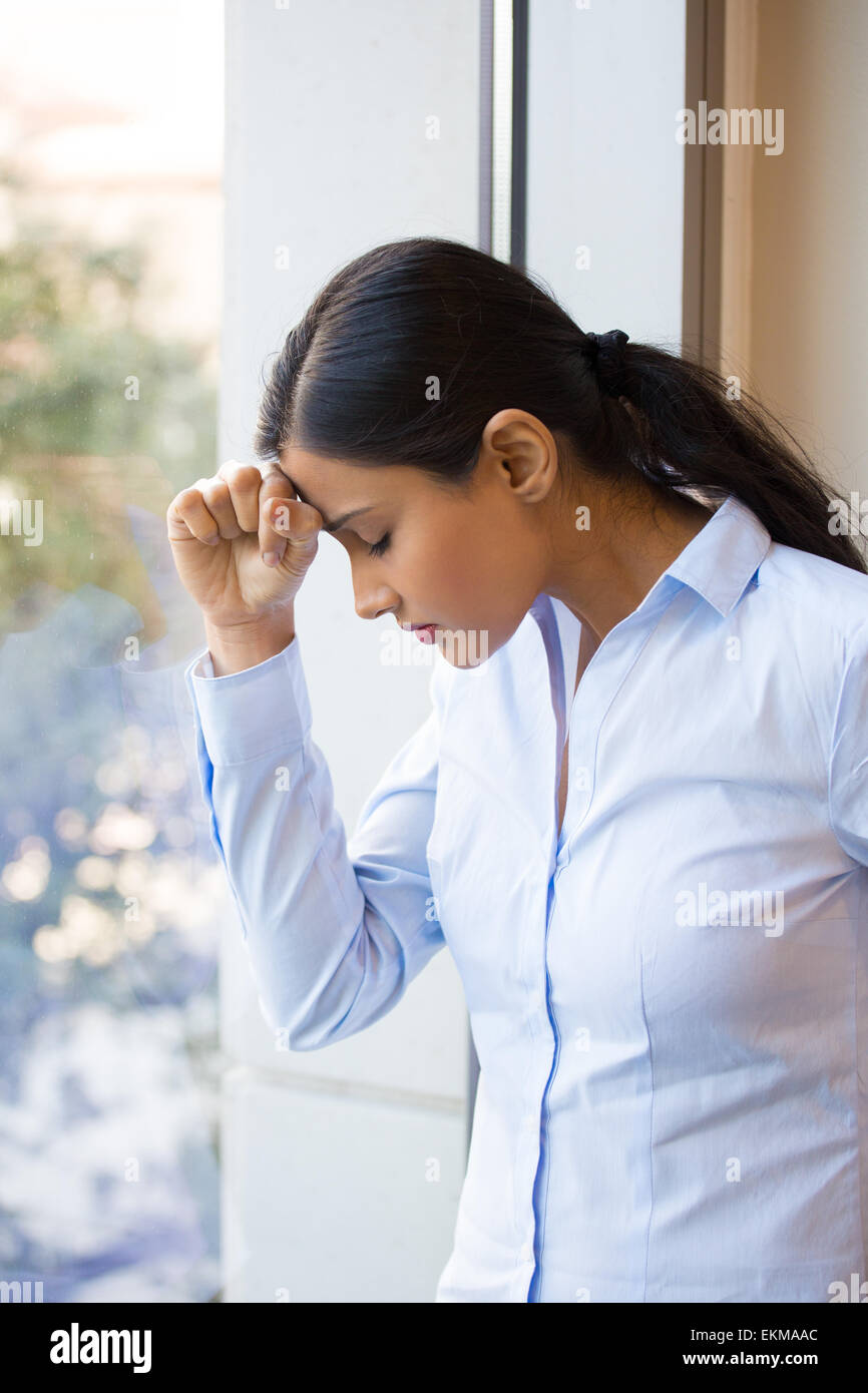 Closeup portrait, sad young woman in blue shirt, head on hand on window, really depressed, down about something, - Stock Image