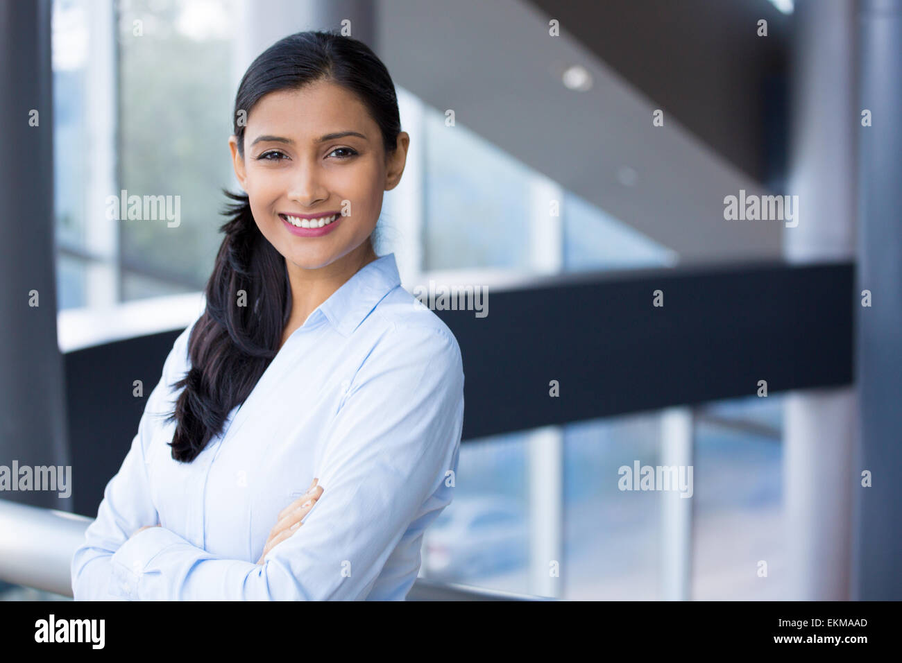 Closeup portrait, young professional, beautiful confident woman in blue shirt, arms crossed folded, smiling isolated - Stock Image