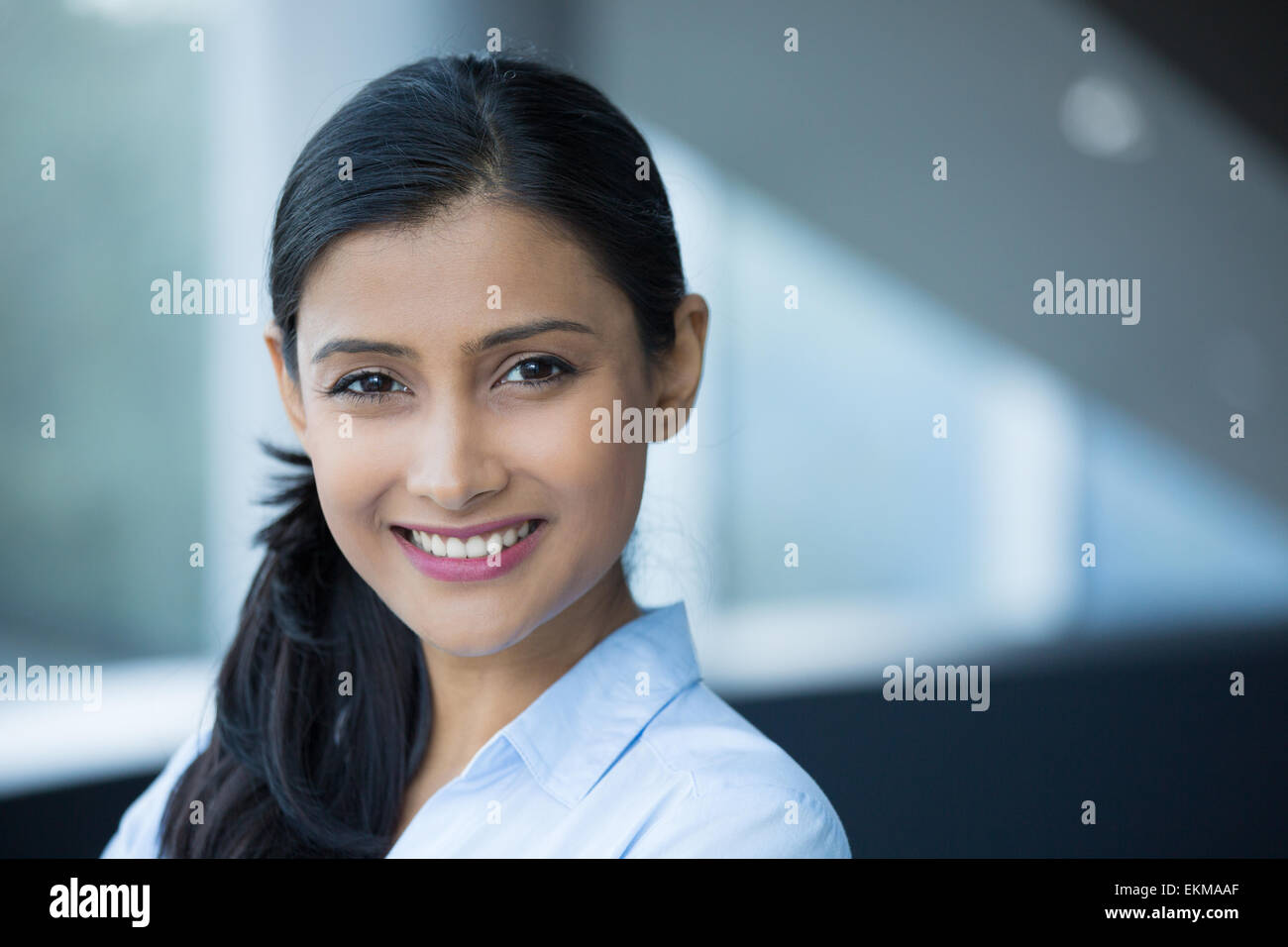 Closeup portrait, young professional, beautiful confident woman in blue shirt, friendly personality, smiling isolated - Stock Image