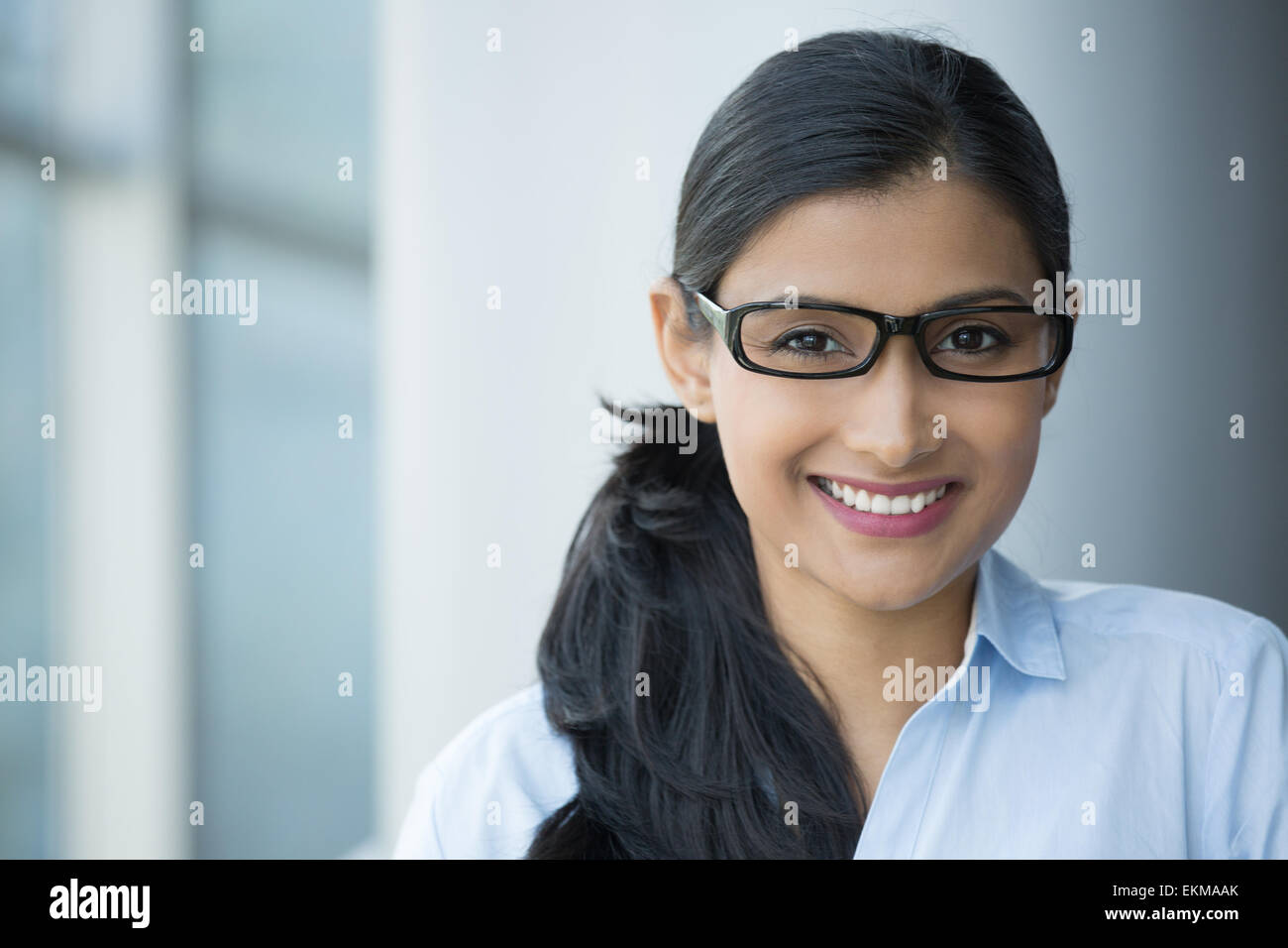 Closeup portrait, young professional, beautiful confident adult woman in blue shirt, with black glasses, smiling - Stock Image