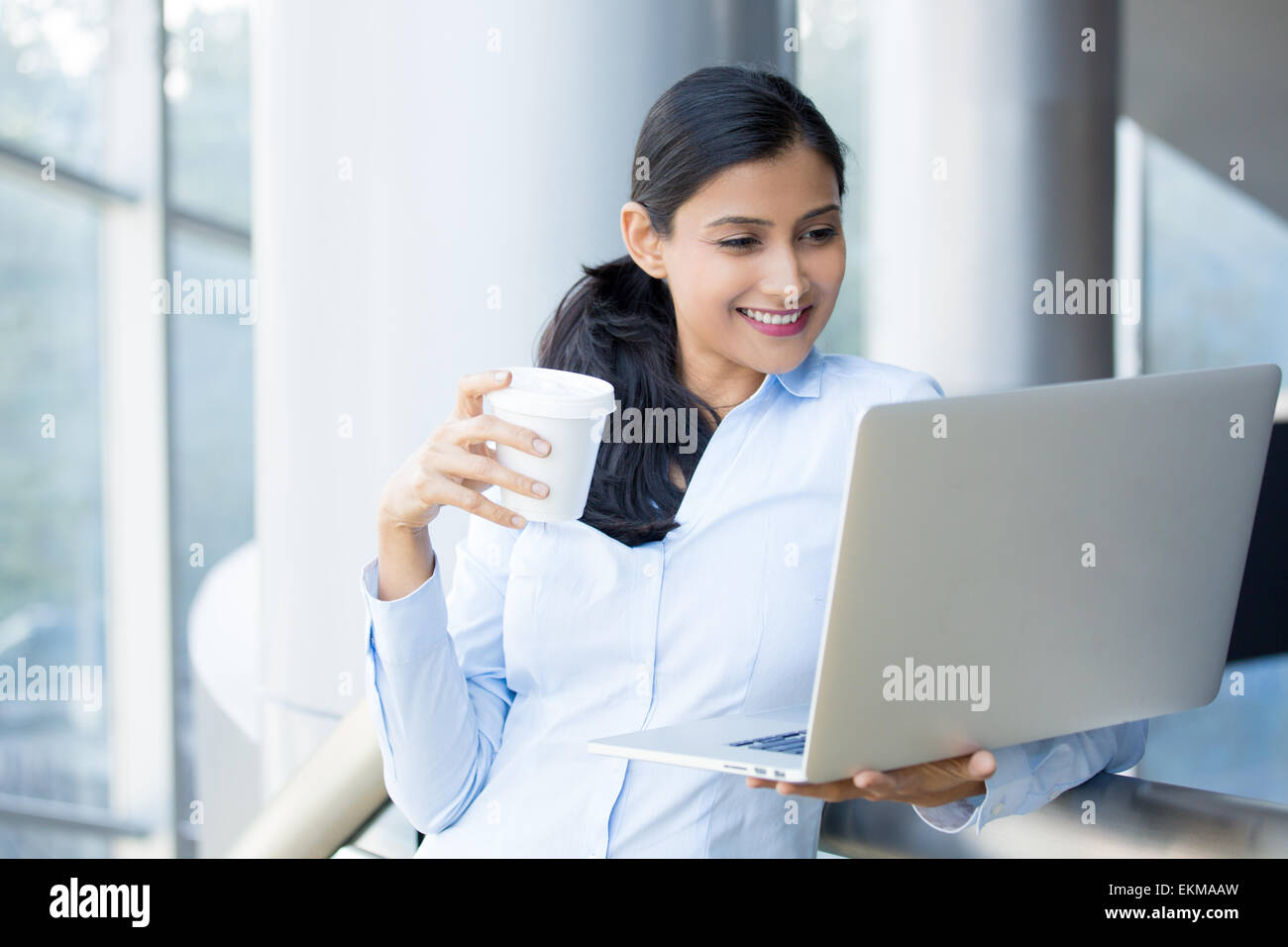 Closeup portrait, young, attractive woman standing, drinking coffee, smiling looking, surfing the silver laptop. - Stock Image