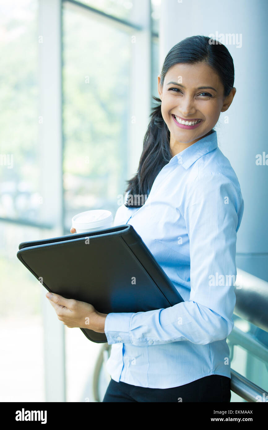 Closeup portrait, young professional, beautiful confident woman in blue shirt, holding coffee and black notebook - Stock Image