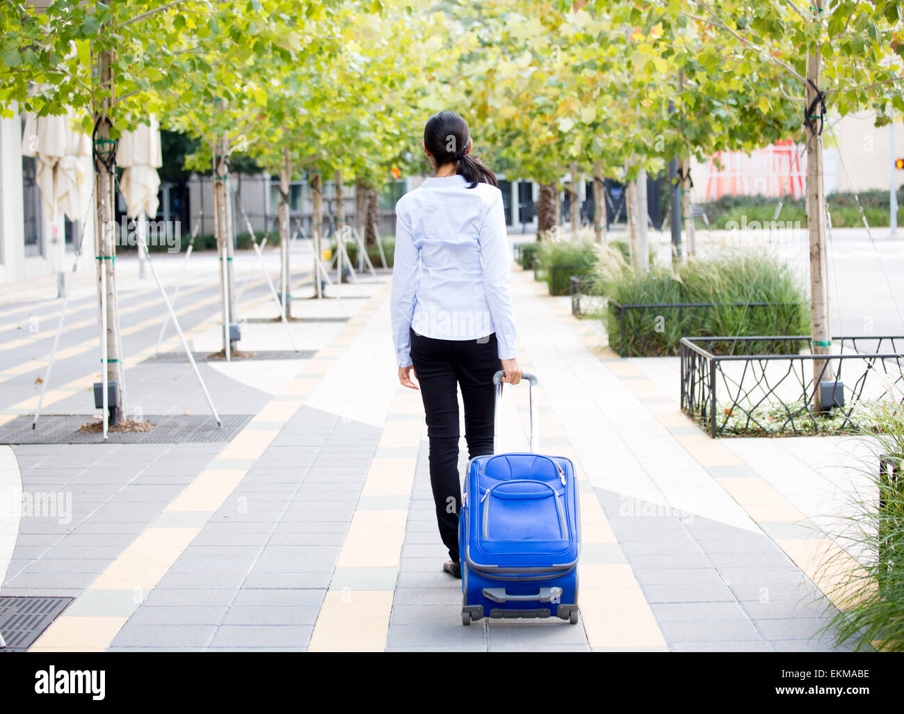 Closeup abstract backside view portrait of woman in light blue shirt carrying luggage, walking through gray sidewalk - Stock Image
