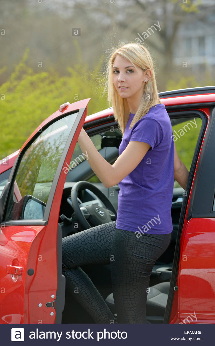 Young woman wearing leggings at a red car in spring - Stock Image