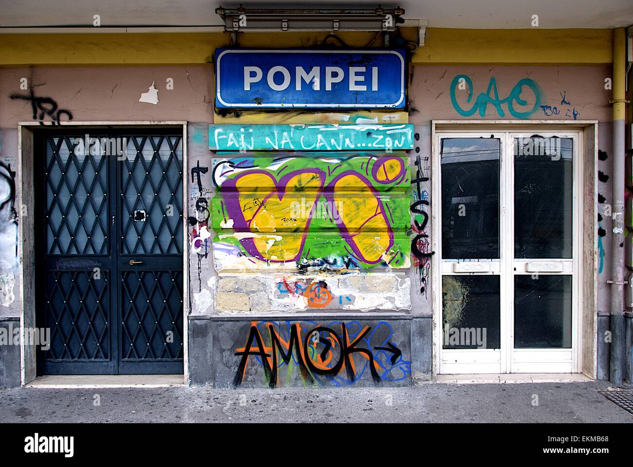 Graffiti on Pompei Sanctuary train station platform in Italy with two doors to the ticket hall and waiting area & Graffiti on Pompei Sanctuary train station platform in Italy with ...