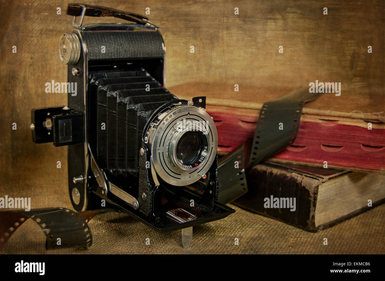 Vintage bellows camera, film and old books with texture overlay. - Stock Image