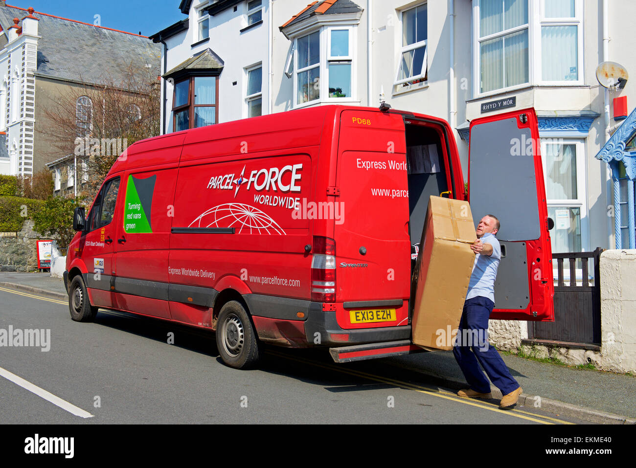 Man unloading large package from Parcel Force delivery van - Stock Image