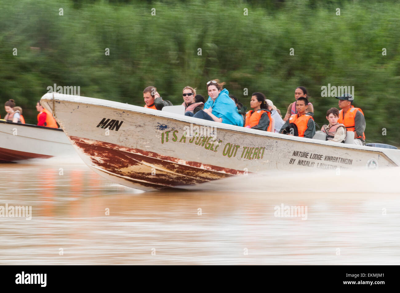 Young travellers in group explore Borneo rainforest in speed boats, Malaysia - Stock Image
