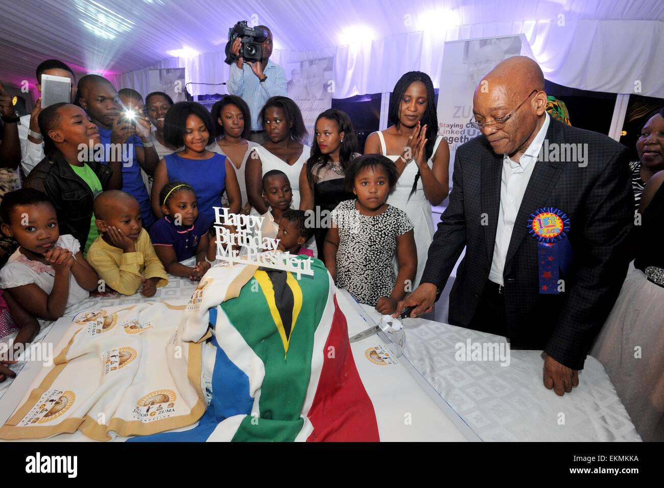 Durban, South Africa. 12th Apr, 2015. South Africa's President Jacob Zuma (1st R) tries to cut the birthday - Stock Image