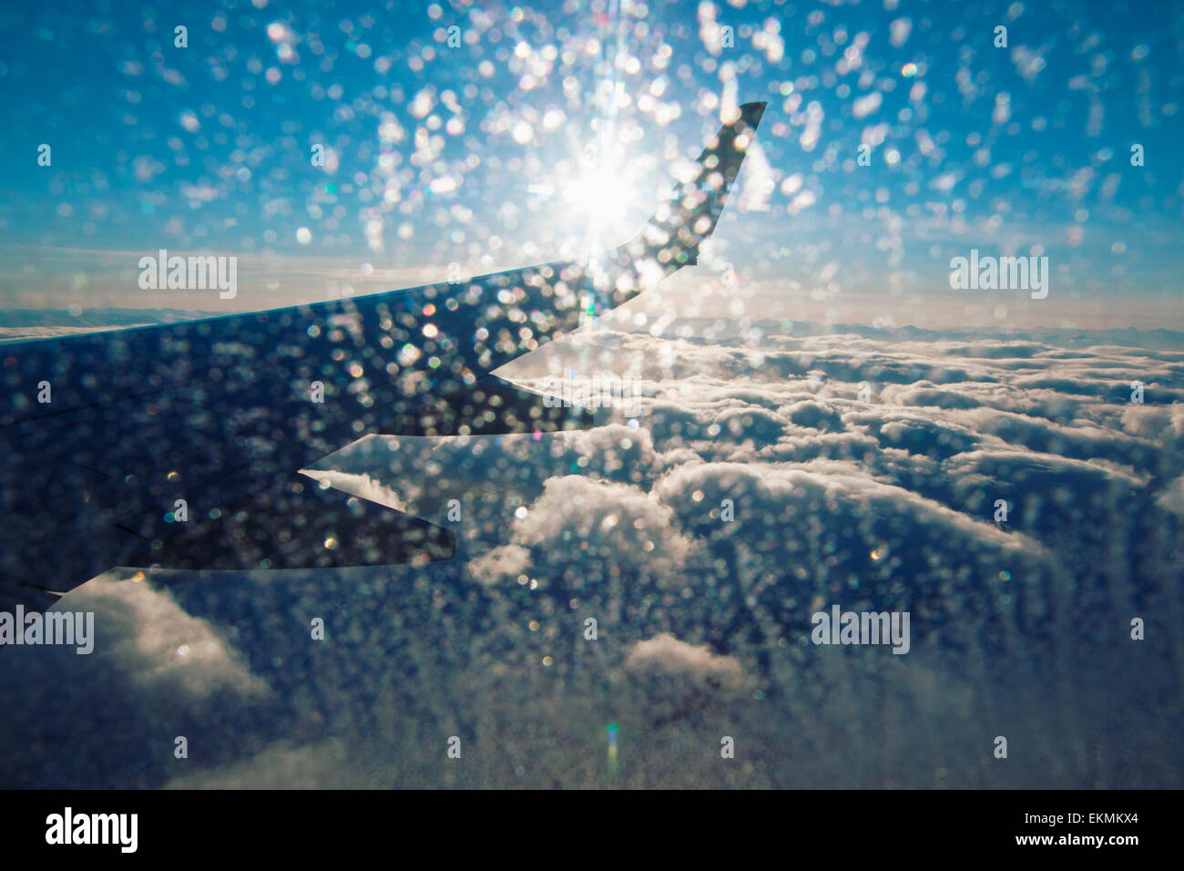 View of airplane wing  and clouds from inside cabin on sunny day with ice on the window. - Stock Image