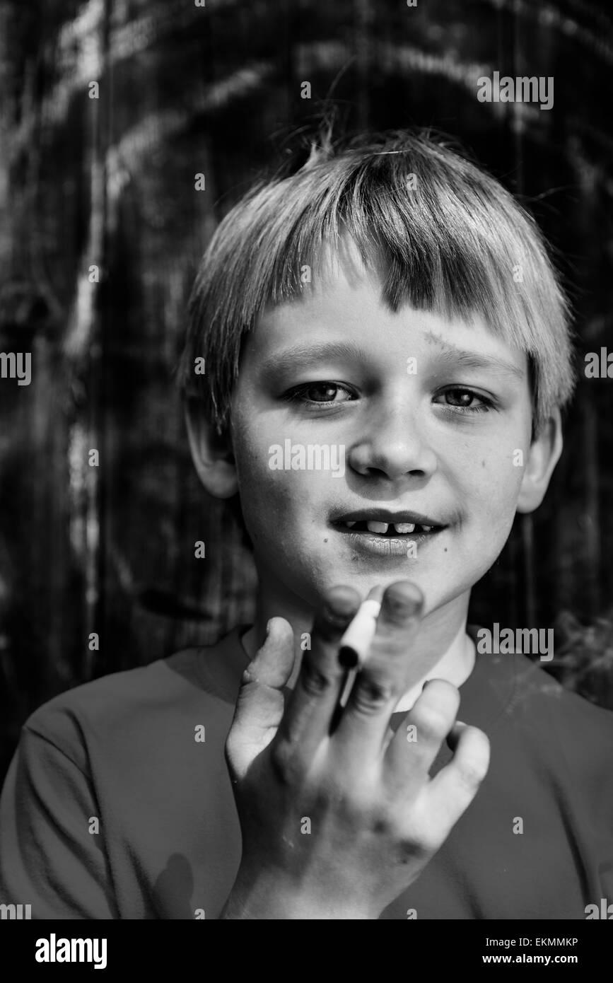 Portrait of Child blond boy smoking cigarette with dark wooden background behind him - Stock Image