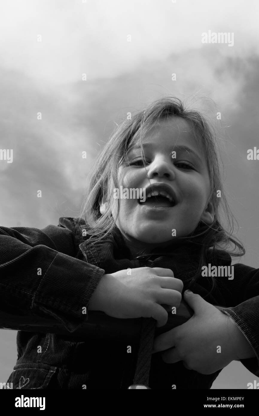 Black and white photo of a 6 year old girl with a tooth missing. Taken from below with clouds in the background. - Stock Image