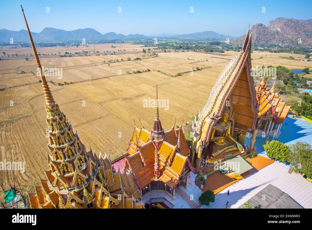 A view from the top of the pagoda, golden buddha statue with rice fields and mountain, Wat Tham Sua(Tiger Cave Temple), - Stock Image