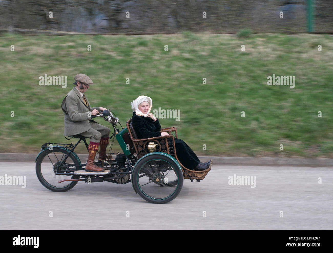 Older couple riding a motor tandem tricycle, a 1903 Phoenix Trimo, Great North Steam Fair, Beamish Museum, England Stock Photo