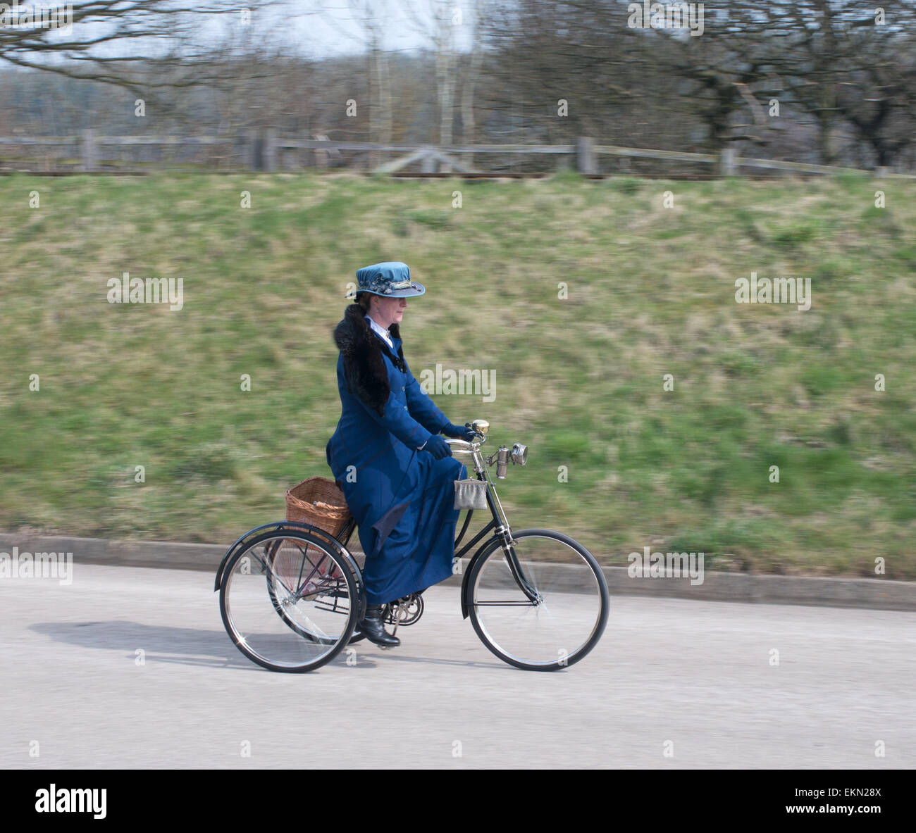 Panned shot of Woman riding vintage tricycle at the Great North Steam Fair, Beamish Museum, England UK - Stock Image
