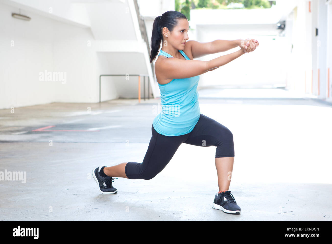 Beautiful hispanic sport woman demonstrating tai chi stance with pretend sword, outdoor. Concept of healthy lifestyle. - Stock Image